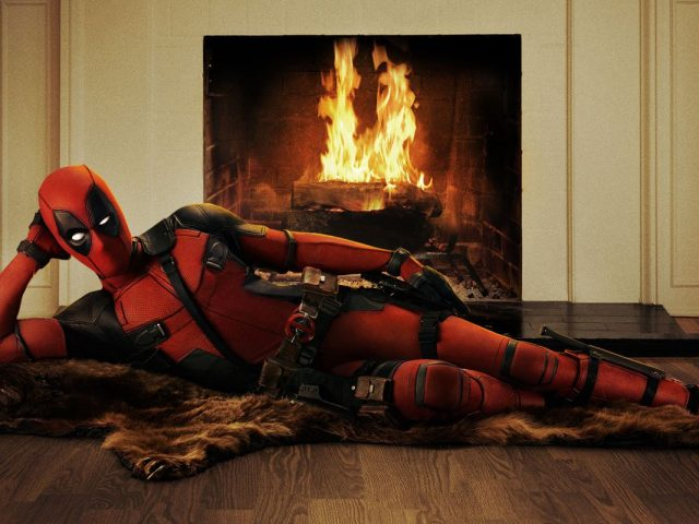 Ryan Reynolds kot Deadpool pred kaminom.