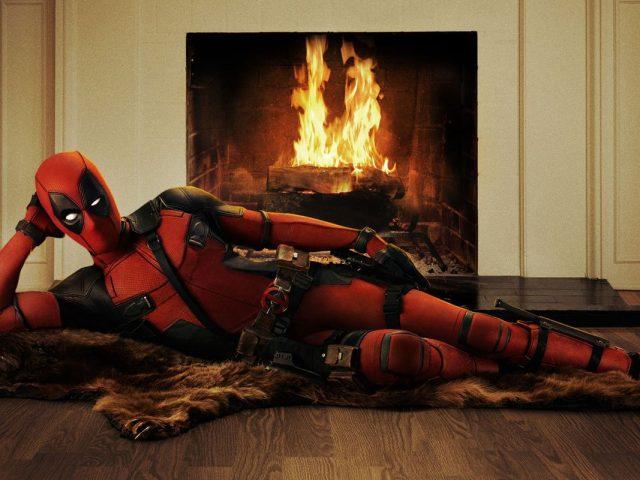 Ryan Reynolds kot Deadpool pred kaminom.